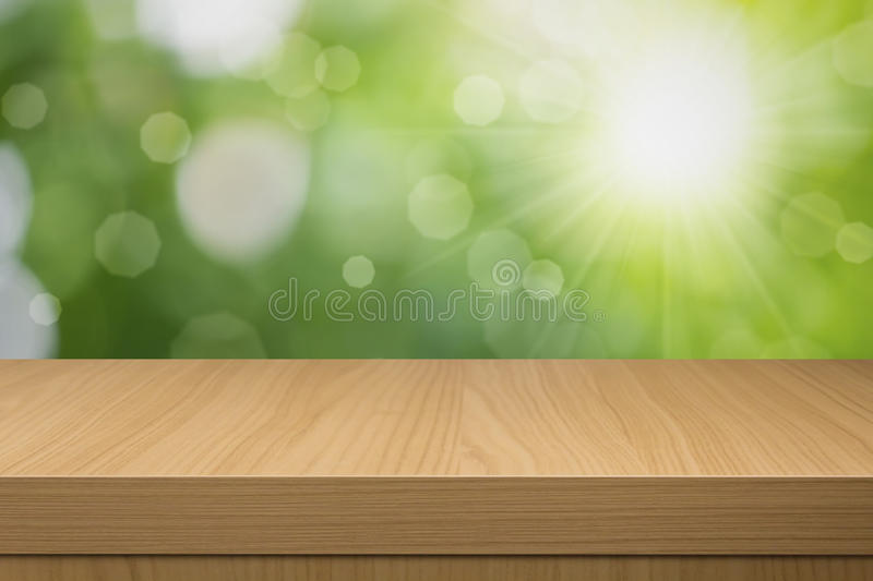 Foliage bokeh background with empty wooden table. royalty free stock images