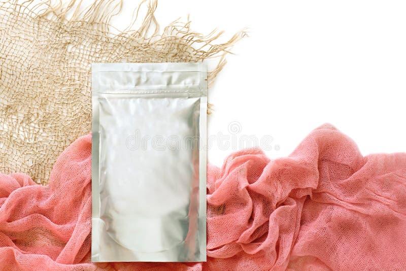 Folie die voor losse cosmetischee producten verpakken, met een roze sticker, doek en droge bloemen, natuurlijke kleuren isoleer,  royalty-vrije stock fotografie
