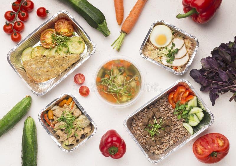 Foliecontainers met gezond voedsel op witte achtergrond royalty-vrije stock foto's