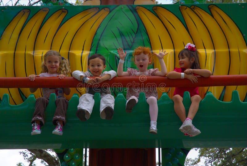 Folk-barn på en nöjesfältritt med lyckliga framsidor royaltyfri foto