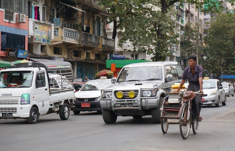 Folk, bilar och cyklar på gatorna i Mandalay arkivbilder