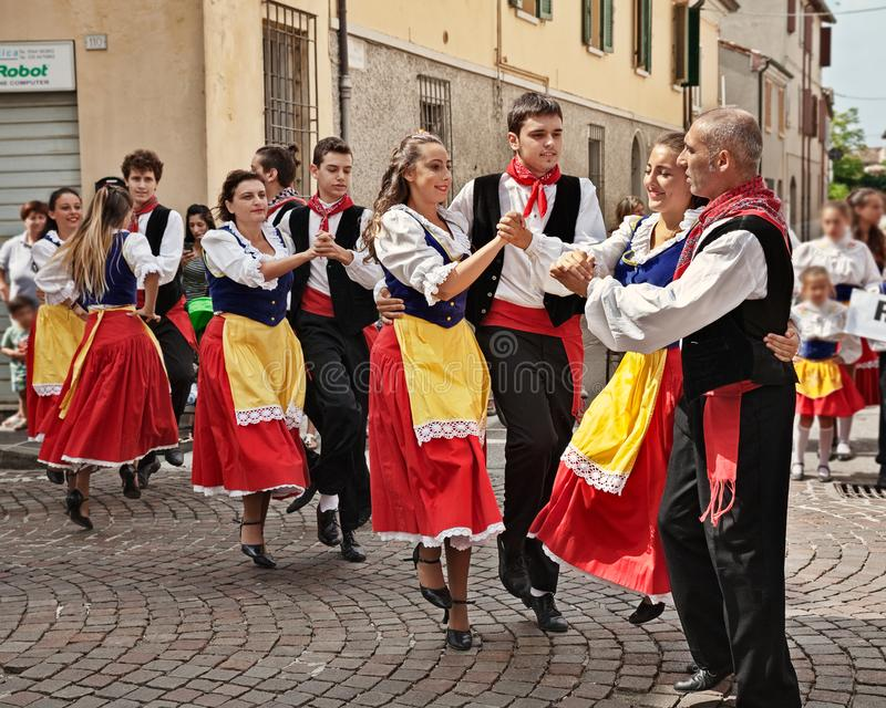 Folk dance ensemble from Romagna, Italy. Folk ensemble Gruppo Folkloristico Canterini Romagnoli performs traditional Romagna dance in the town street during the stock photography