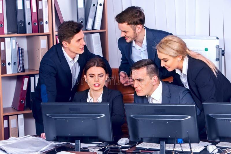Folk för lag för affärsfolk som arbetar med legitimationshandlingar vid datorbildskärmen arkivfoton