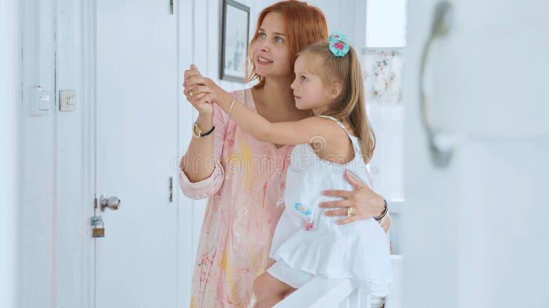 Folk, familj och gyckelbegrepp - lycklig flicka som spenderar tid med den hemmastadda modern royaltyfria bilder