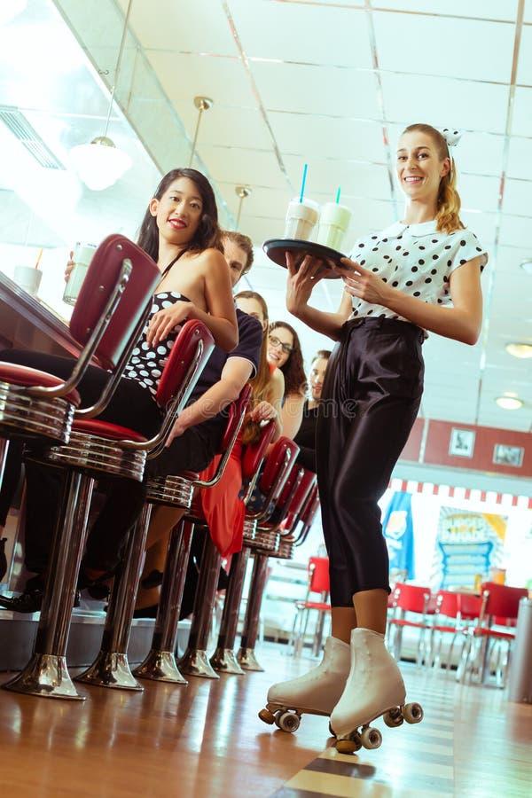 Folk i amerikansk matställe eller restaurang med servitrins royaltyfria bilder