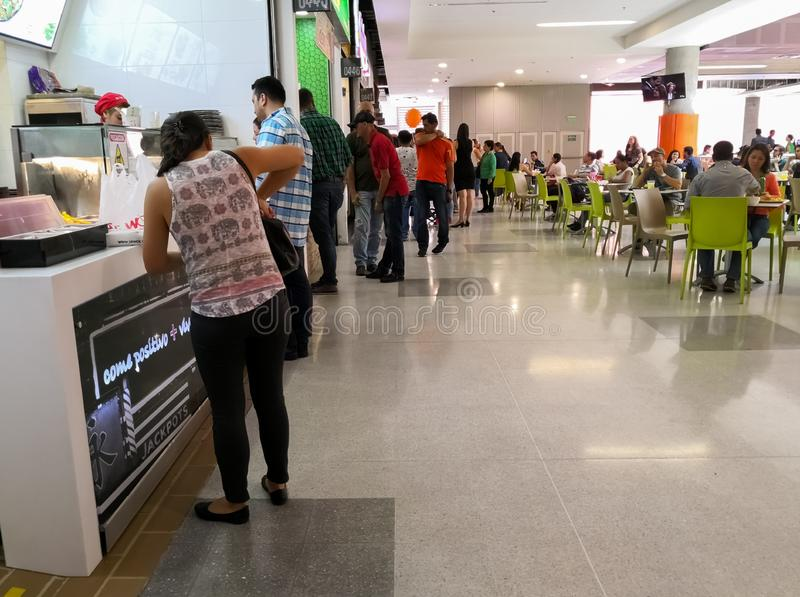 Folk i en shoppinggalleriaköpande och en beställamat i snabbmatrestauranger arkivbilder