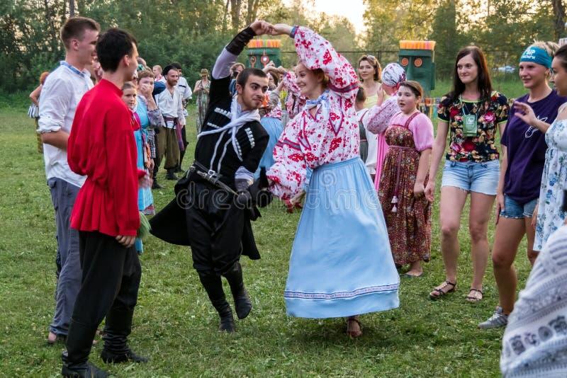 Folk i färgrika folkdräkter som dansar i en folkmassa för tiden av den årliga internationella festivalen arkivbild