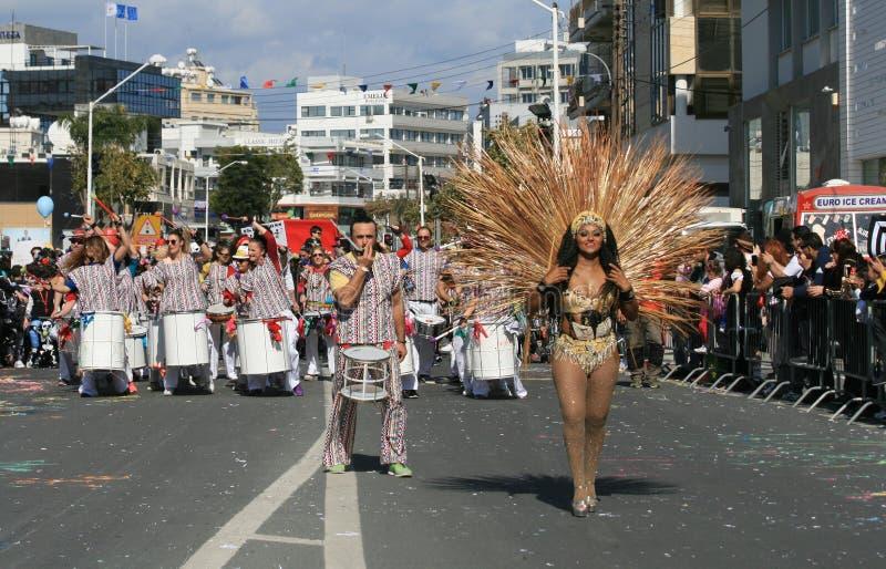 Folk i karnevaldräkter som marscherar längs en gata royaltyfria foton