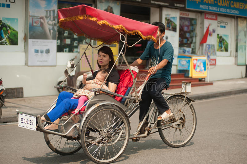 Folk i området som tar en cyclo ritt i Hanoi, Vietnam royaltyfria foton