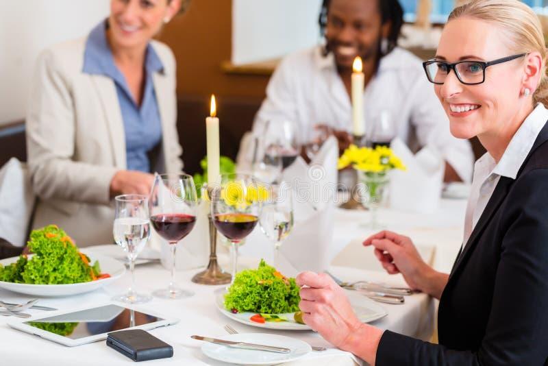 Folk i restaurang på samtal för affärslunch royaltyfria bilder