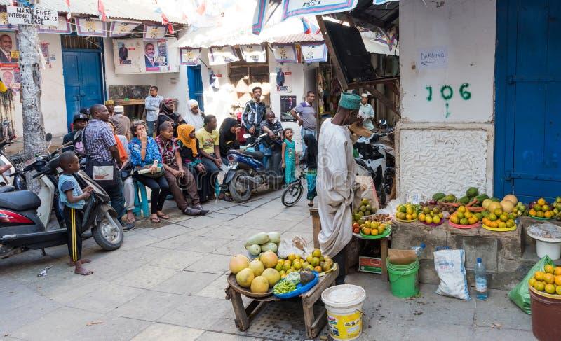 Folk i Zanzibar stadgata med grönsakförsäljning på hörnet arkivbild
