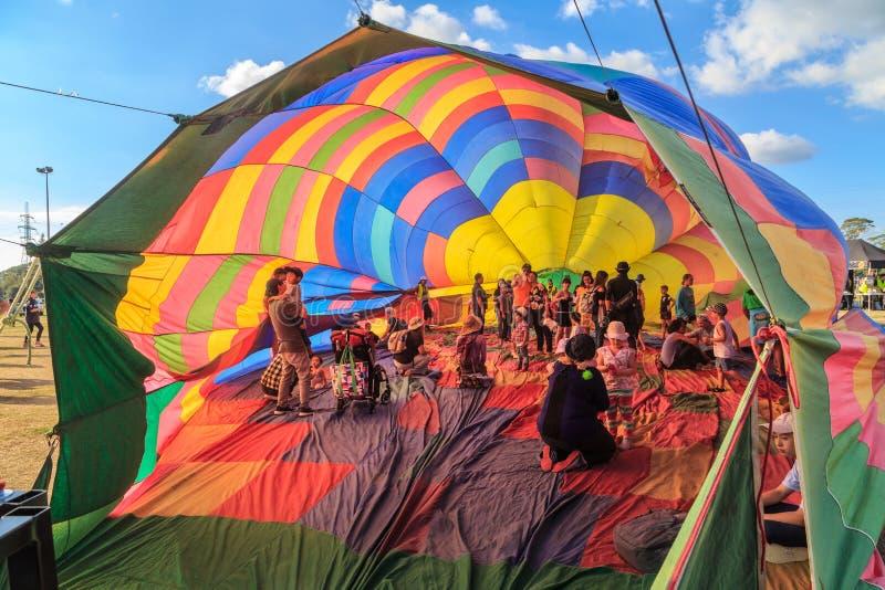 Folk inom ballong för varm luft för halva en uppblåst arkivbilder