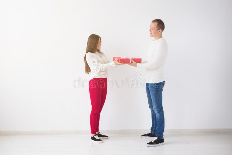 Folk-, jul-, födelsedag-, ferie- och valentin dagbegrepp - den stiliga mannen ger på hans flickvän en gåvaask royaltyfri fotografi