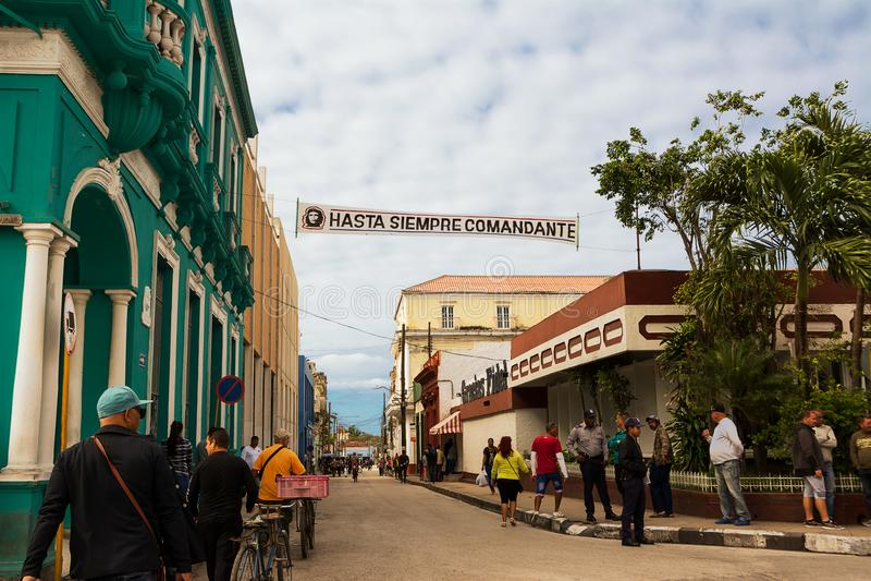 Folk längs en gata av Santa Clara med ett baner som visar Iet arkivbild
