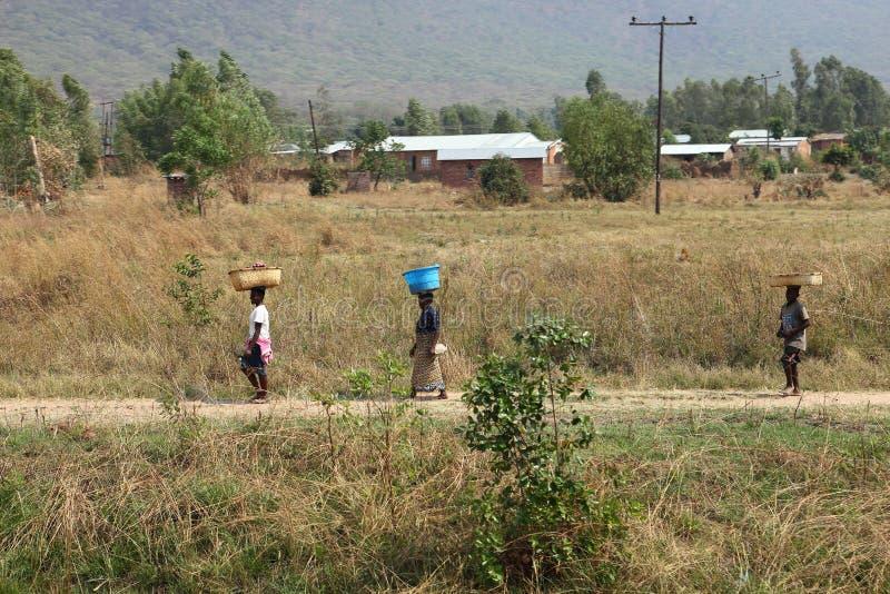 Folk längs en väg i Malawi royaltyfria bilder