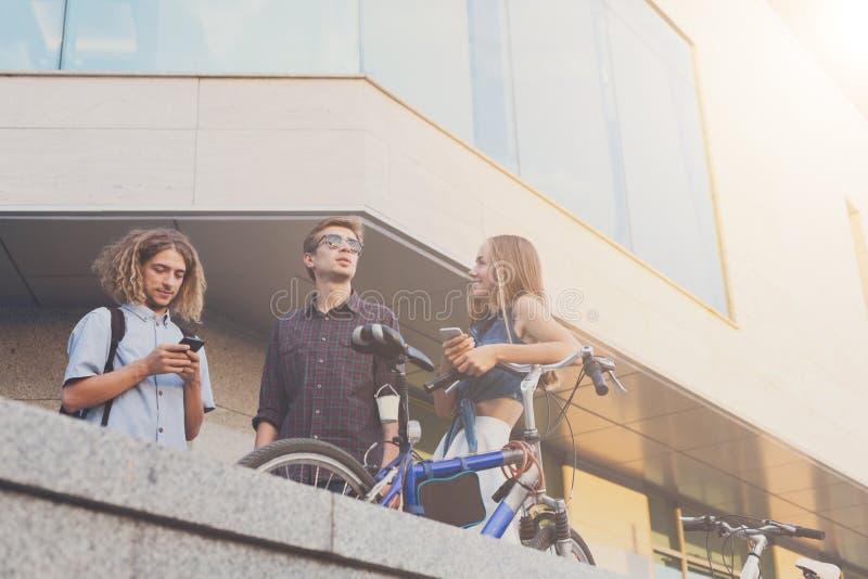 Folk med cyklar och smartphones arkivfoto