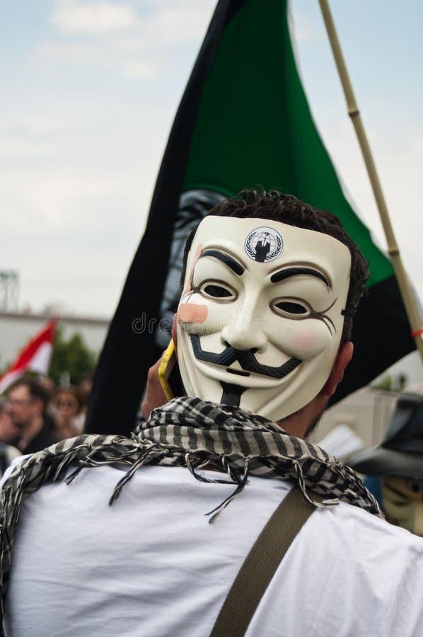 Folk med den anonyma maskeringen under demonstrationen mot Monsanto och transatlantiquen t fotografering för bildbyråer
