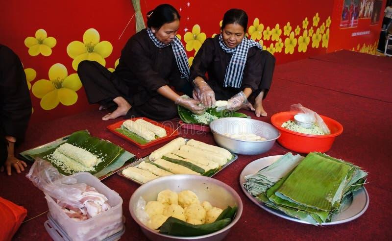 Folk med den traditionella vietnamesiska klänningen som gör traditionell mat royaltyfri bild