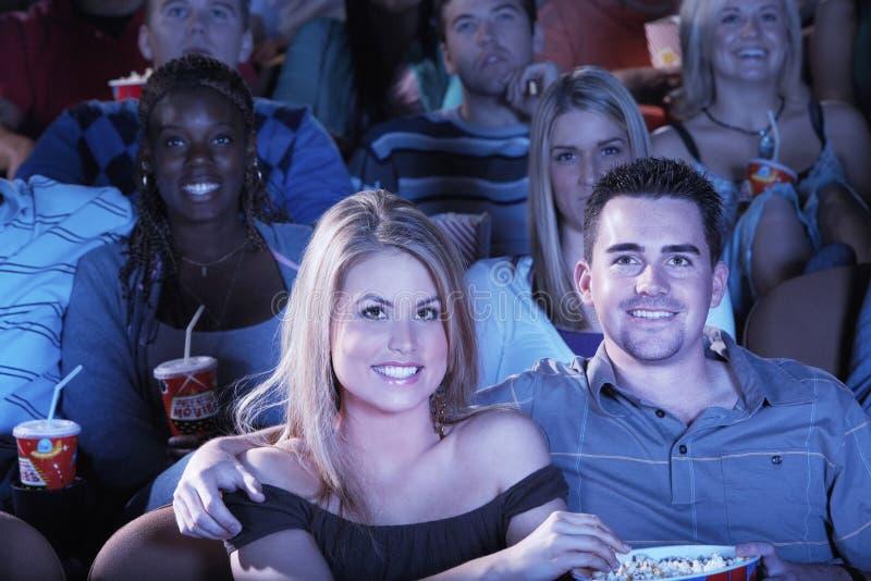 Folk med hållande ögonen på film för sodavatten och för popcorn i teater arkivbilder