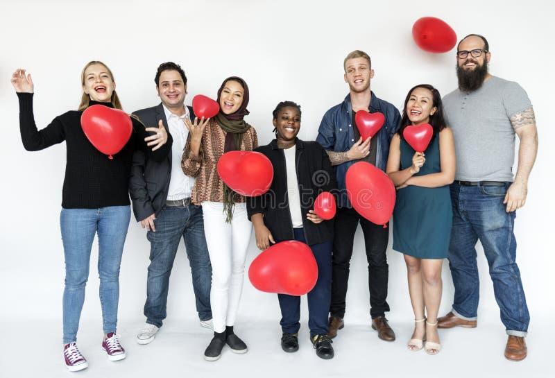 Folk med hjärta formade ballonger arkivbild