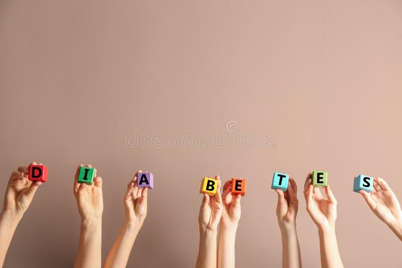 Folk med kuber som bildar ordet SOCKERSJUKA på färgbakgrund arkivbilder