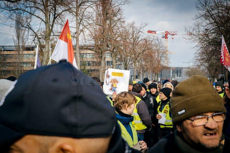 Folk med plakatet som protesterar den gula västmarschen royaltyfri fotografi