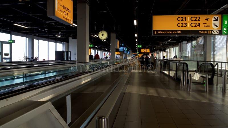 Folk med resväskor som går till avvikelsekorridoren på flygplatsterminalen som reser fotografering för bildbyråer
