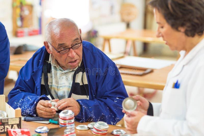 Folk med speciala behov eller handikapparbete med deras lärare på seminariet av yrkes- terapi arkivfoto