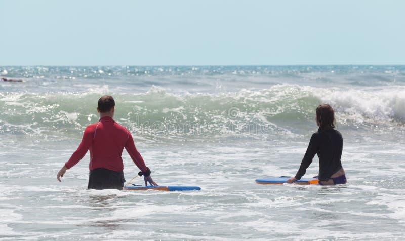 Folk med surfingbrädor royaltyfri fotografi