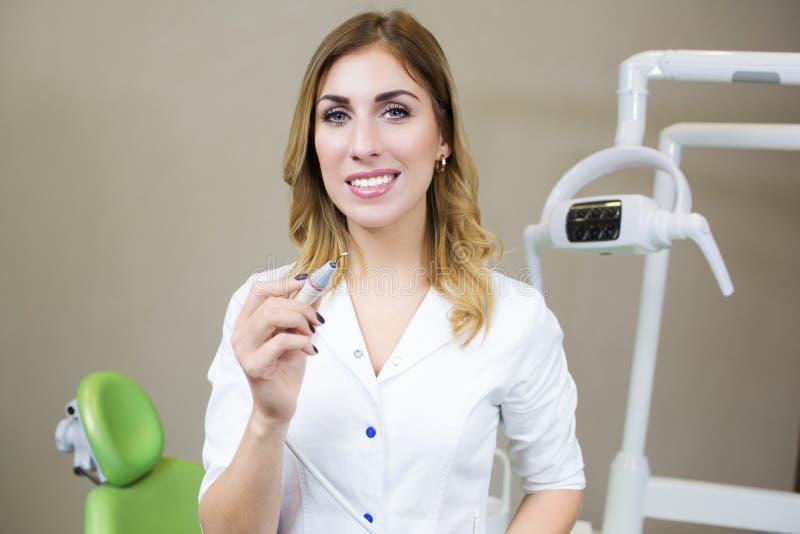 Folk-, medicin-, stomatology- och sjukvårdbegrepp - lycklig ung kvinnlig tandläkare med hjälpmedel över medicinsk kontorsbakgrund royaltyfri fotografi