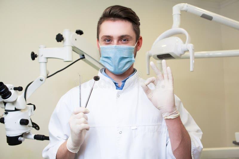 Folk-, medicin-, stomatology- och sjukvårdbegrepp - lycklig ung manlig tandläkare med hjälpmedel över medicinsk kontorsbakgrund arkivfoto