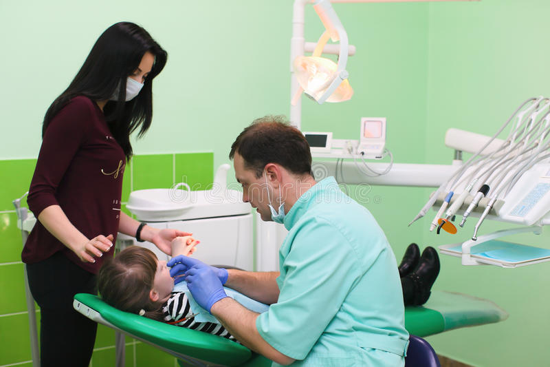 Folk-, medicin-, tandläkekonst- och hälsobegrepp - en kvinnapatient som ser barnet som en tandläkare för att behandla hennes barn royaltyfri bild