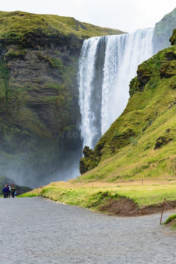 Folk nära den Skogafoss vattenfallet i Island royaltyfri fotografi