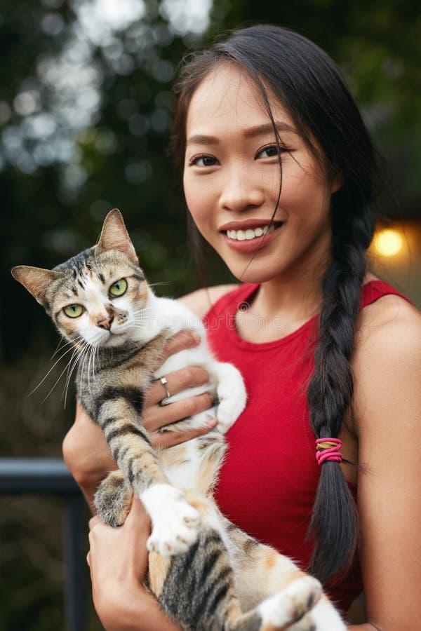 Folk och djur Härlig asiatisk kvinna med katten royaltyfri bild