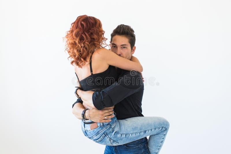Folk- och förälskelsebegrepp - härlig nätt kvinna som sitter på mannen och omfamnar honom arkivfoto