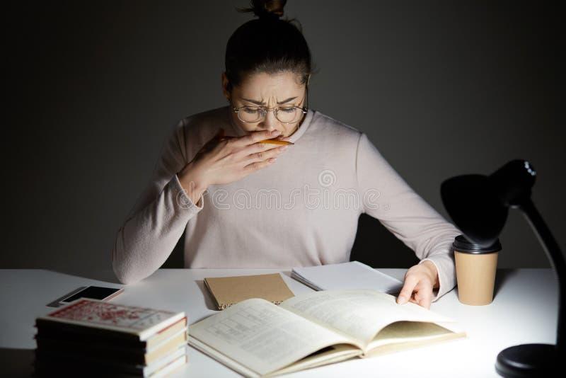 Folk- och trötthetbegrepp Sömniga studentgäspningar, poserar på skrivbordet, arbetsövertid, under natt, förbereder sig för komman royaltyfria foton