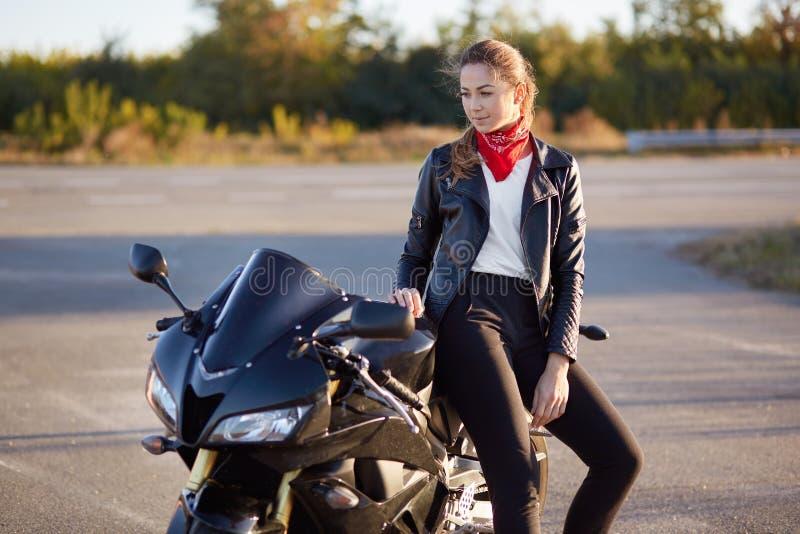 Folk och transportbegrepp Den härliga unga kvinnan i svarta stilfulla cyklister beklär, lutar på den snabba mopeden, har fundersa arkivfoton