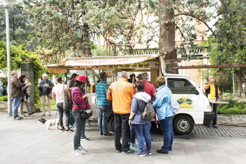 Folk- och utlänninghandelsresande som köper mat, åker lastbil på den Meran staden arkivbilder