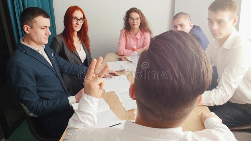 Folk på affärskonferensen som talar vid tabellen En chef som talar till dem royaltyfria bilder