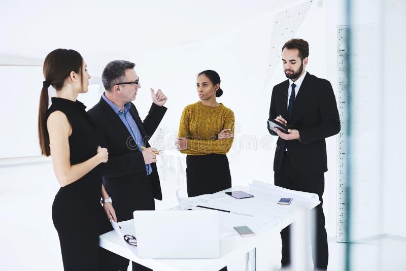 Folk på arbete med anställda i coworking utrymme genom att använda modern apparater och wifi royaltyfri foto