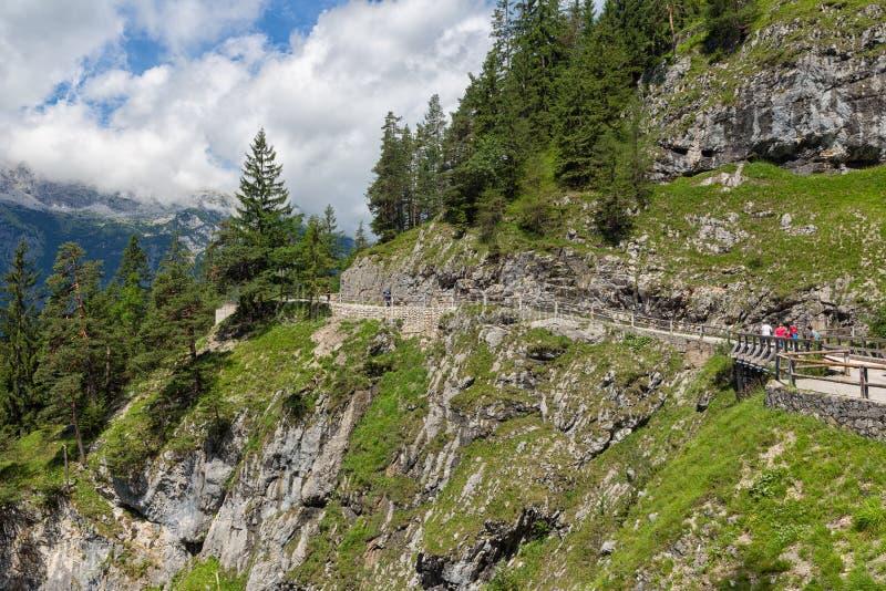 Folk på att fotvandra slingan till och med österrikiska berg till isgrottan royaltyfri bild