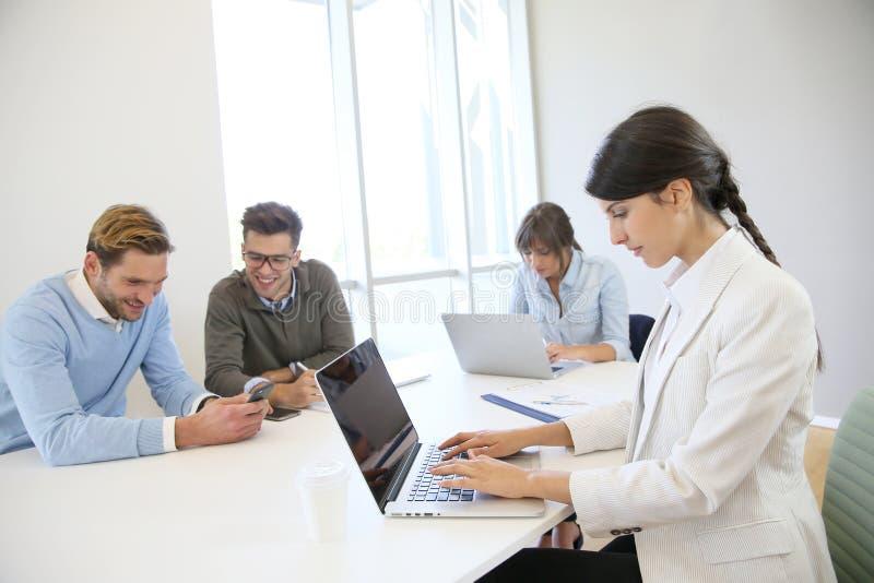 Folk på datorer som arbetar i start-up företag royaltyfri bild