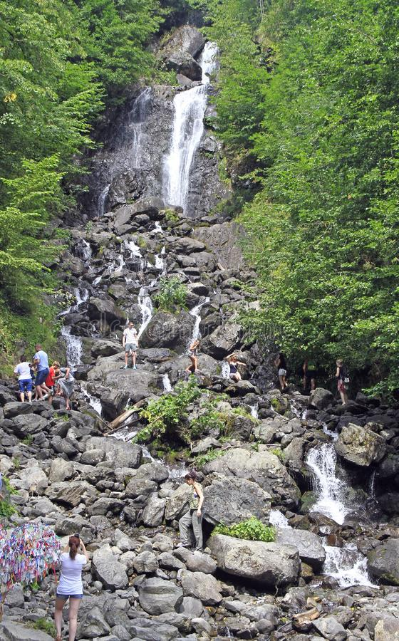 Folk på den mjölkaktiga vattenfallet i Abchazien fotografering för bildbyråer