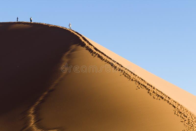Folk på en röd dyn i den Namib öknen, i Sossusvlei, Namibia royaltyfri bild