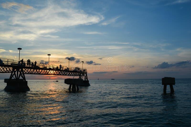 Folk på fiskepir på solnedgången arkivbild