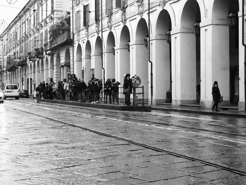 Folk på hållplatsen in via Po i Turin, Italien i svartvitt arkivbild