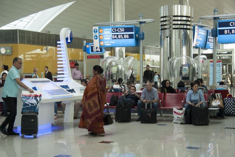 Folk på informationsställningen i väntande vardagsrum för flygplats royaltyfri foto