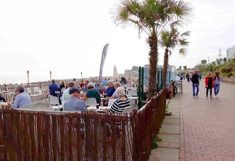 Folk på kafét på Eastbourne promenad royaltyfri foto