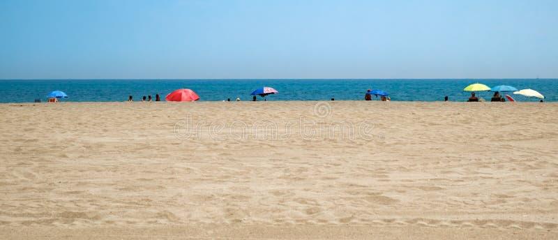 Folk p? kanten av stranden royaltyfri foto