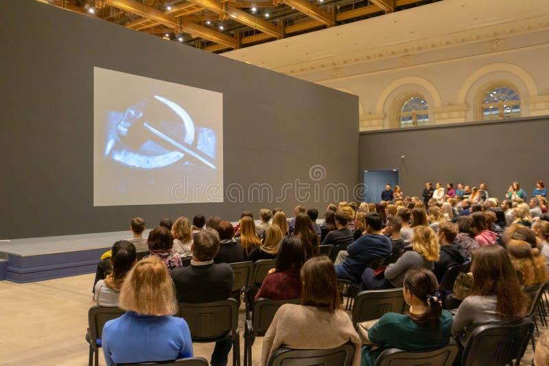 Folk på konferensen av historia som lyssnar och håller ögonen på skärmen tillbaka sikt Horisontalbildsammans?ttning arkivbilder